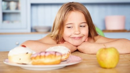 Girl Sitting At Table Choosing Cakes Or Apple For Snack